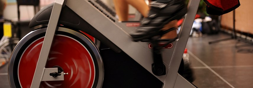 close up of feet operating an exercise spinning bike