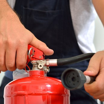 close up of hands holding a fire extinguisher