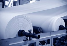 close up of white rolls of material in a factory