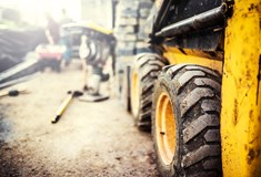 close up of worksite vehicle tyres with other tools in distant blurred background